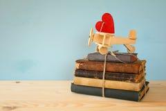 Avion en bois avec le coeur sur la pile de vieux livres Photo libre de droits