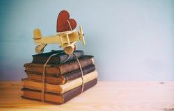 Avion en bois avec le coeur sur la pile de vieux livres Image stock