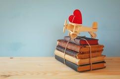 Avion en bois avec le coeur sur la pile de vieux livres Photo stock