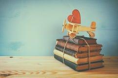 Avion en bois avec le coeur sur la pile de vieux livres Photos libres de droits