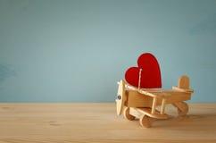 Avion en bois avec le coeur sur la table Photo stock