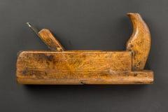 Avion en bois de vieil outil de charpentier sur un gris Image stock