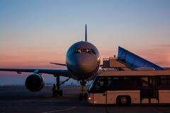 Avion et autobus sur le tablier d'aéroport de début de la matinée Photographie stock