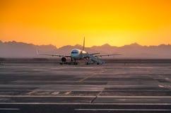 Avion le soir contre le contexte des montagnes Photographie stock libre de droits