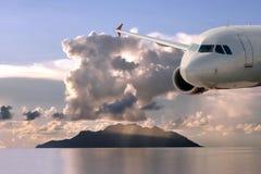 Avion, nuages, île, mer   Photographie stock libre de droits