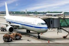 Avion près du terminal dans un aéroport sous le ciel bleu Photographie stock libre de droits