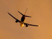 Avion quittant l'aéroport au coucher du soleil Images stock