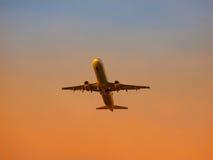 Avion quittant l'aéroport au coucher du soleil Photographie stock libre de droits