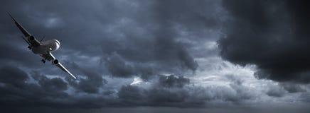 Avion à réaction dans un ciel orageux foncé Image stock