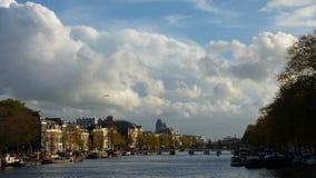 Avion silhouetté contre les nuages au-dessus de Grand Canal à Amsterdam, Pays-Bas Image stock