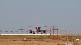 Avion sur la piste avec des lumières de piste dans le premier plan photographie stock