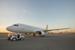 Avion sur la piste d'aéroport au coucher du soleil Images stock