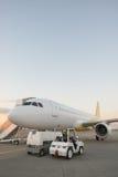 Avion sur la piste d'aéroport au coucher du soleil Photos stock
