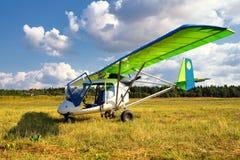 Avion ultra-léger de poids sur un champ d'herbe Photos stock
