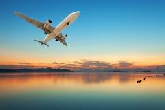Avion volant au-dessus de la mer tropicale au beau coucher du soleil ou lever de soleil Photographie stock