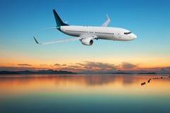 Avion volant au-dessus de la mer tropicale au beau coucher du soleil ou lever de soleil Photos stock