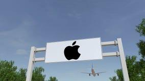 Avion volant au-dessus du panneau d'affichage de publicité avec Apple Inc logo Entrée moderne d'immeuble de bureaux Rendu 3D édit Images stock