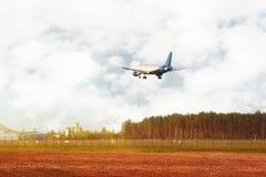 Avion volant en bas du champ et de la forêt proches Image stock