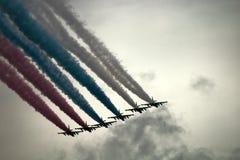 Aviones de ataque rusos SU-25, aviones con la estela de vapor coloreada Colores de la bandera rusa Imágenes de archivo libres de regalías