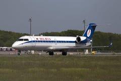 Aviones de Belavia Canadair CRJ-100ER que se preparan para el despegue de la pista Imagen de archivo