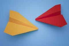 Aviones de papel amarillos y rojos en un fondo azul Imágenes de archivo libres de regalías