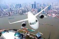 Aviones de pasajero en vuelo sobre la ciudad Imagenes de archivo