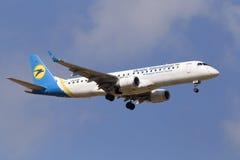 Aviones de Ukraine International Airlines Embraer ERJ190-100 del aterrizaje en el fondo del cielo nublado Imagen de archivo