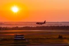 Aviones del aterrizaje en el carmesí de la mañana Fotografía de archivo