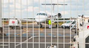 Aviones del mantenimiento en la pista de despeque detrás de una barrera Imagenes de archivo