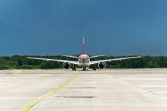 Aviones en la pista de la dirección en el aeropuerto, exactamente en el centro en el marco, visión trasera imagenes de archivo
