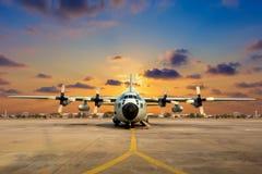 Aviones militares en la pista durante puesta del sol Foto de archivo