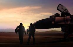Aviones militares y piloto en el campo de aviación en escena de la silueta imagen de archivo