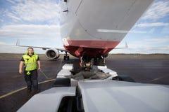 Aviones que hacen una pausa del trabajador de tierra con el cable de la comunicación en R imagen de archivo