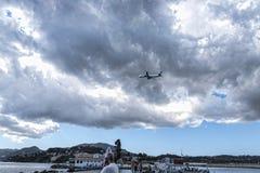 Aviones que sacan o que aterrizan en Kanoni, sobre la iglesia de Panagia Vlacherna y la isla del ratón en la isla griega de Corfú Imagen de archivo libre de regalías