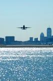 Aviones que salen con horizonte de la ciudad Fotografía de archivo