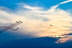 Avions acrobatiques dans l'action à un vol d'Airshow au coucher du soleil/au crépuscule Images stock