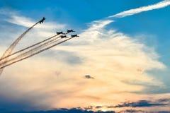 Avions acrobatiques dans l'action à un vol d'Airshow au coucher du soleil/au crépuscule Photos stock