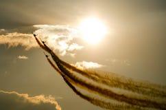 Avions acrobatiques fumeux sur le coucher du soleil Images libres de droits