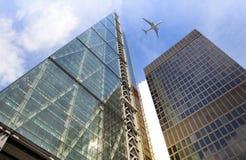 Avions au-dessus des gratte-ciel de Londres allant débarquer dans l'aéroport de ville Photographie stock