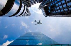 Avions au-dessus des gratte-ciel de Londres allant débarquer dans l'aéroport de ville Image stock