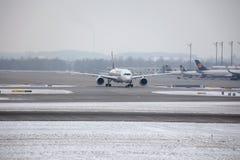 Avions aux portes terminales dans l'aéroport de Munich, horaire d'hiver avec la neige Photographie stock libre de droits