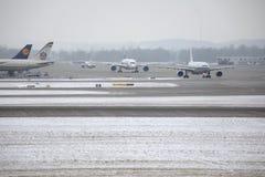 Avions aux portes terminales dans l'aéroport de Munich, horaire d'hiver avec la neige Photos stock
