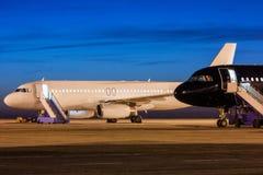 Avions blancs et noirs de passager sur le tablier de l'aéroport au crépuscule Images libres de droits