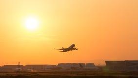 Avions démarrant le soir d'un aéroport Images libres de droits
