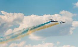 Avions dans le ciel avec de la fumée colorée de Photos stock