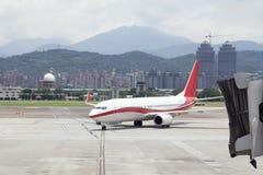 Avions de approche avec le jetbridge dans la chanson Shan Airport de Taïpeh Photo stock
