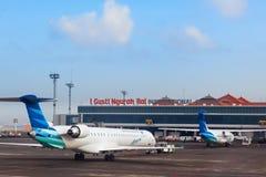 Avions de Garuda dans l'aéroport international de Denpasar Ngurah Rai sur Bali Image libre de droits