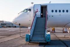 Avions de transport de passagers avec des escaliers d'embarquement au tablier d'aéroport et reliés à un bloc d'alimentation exter Photo stock