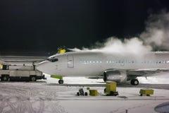 Avions de transport de passagers de dégivrage la nuit Photographie stock libre de droits