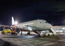 Avions de transport de passagers d'assistance en escale à l'aéroport d'hiver de nuit Photographie stock libre de droits